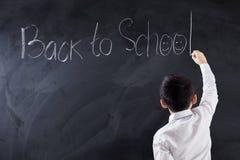 Dziecko pisze tekscie Z powrotem szkoła w klasie Obrazy Royalty Free