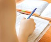 Dziecko pisze w notatniku Zdjęcia Royalty Free
