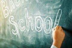 Dziecko pisze z kredą na blackboard tylna tło do szkoły zdjęcia stock