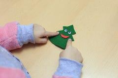 Dziecko pokazuje odczuwaną choinki zabawkę Dziecko trzyma choinki zabawkę w jego ręce fotografia stock