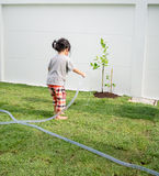 Dziecko pomaga ona rodzice nawadnia rośliny Obrazy Royalty Free