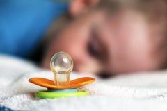 Dziecko pomarańczowy pacyfikator i dziecka dosypianie obraz royalty free