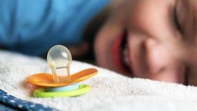 Dziecko pomarańczowy pacyfikator i dziecka dosypianie, uśmiech zdjęcia stock