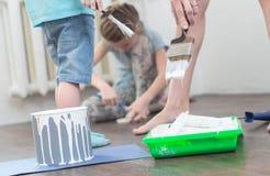 Dziecko pomoc w naprawach: chłopiec i dziewczyna wsadu muśnięcia i rolownik w białą farbę Fotografia Stock