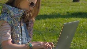 Dziecko pracuje na laptopie w naturze Nastoletnia dziewczyna jest ubranym okulary przeciwsłonecznych siedzi na trawie w parku Dzi zbiory