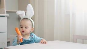 Dziecko preschool wiek z królików ucho na jego głowy obsiadanie w pepinierze i żuć pomarańczowej marchewki zdjęcie wideo