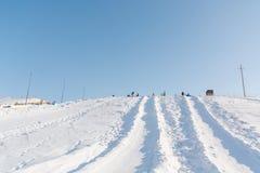 Dziecko przejażdżka na tubingu Zimy rozrywka Narciarstwo w zimie Śnieżna zabawa w zimie Zabawa w zimie tubing Obrazy Royalty Free