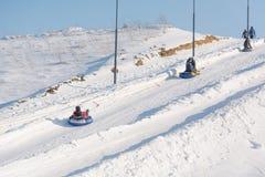 Dziecko przejażdżka na tubingu Zimy rozrywka Narciarstwo w zimie Śnieżna zabawa w zimie Zabawa w zimie tubing Obraz Stock