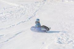 Dziecko przejażdżka na tubingu Zimy rozrywka Narciarstwo w zimie Śnieżna zabawa w zimie Zabawa w zimie tubing Obraz Royalty Free