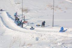 Dziecko przejażdżka na tubingu Zimy rozrywka Narciarstwo w zimie Śnieżna zabawa w zimie Zabawa w zimie tubing Zdjęcia Royalty Free