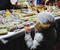 Dziecko przy Kolorowymi miodownikami przy Ryskimi bożymi narodzeniami Wprowadzać na rynek Zdjęcia Stock