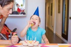 Dziecko przygotowywający dmuchać partyjną dmuchawę obok matki i torta Obraz Royalty Free