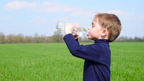 Dziecko quenches pragnienie, napój woda od przejrzystej plastikowej butelki, stoi na zielonym gazonie w zwolnionym tempie, zbiory