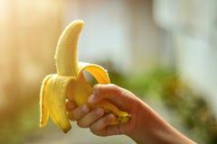 Dziecko ręka trzyma banana odizolowywa zdjęcie stock