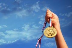 Dziecko ręka podnosząca, trzymający złotego medal przeciw niebu edukaci, sukcesu, osiągnięcia, nagrody i zwycięstwa pojęcie, zdjęcia royalty free