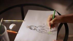 Dziecko ręka rysuje kobiety lekarkę w zielonym ołówku na papierze zbiory wideo