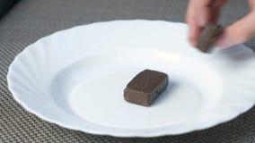 Dziecko ręka stawia czekoladowych cukierki na białym talerzu zbiory