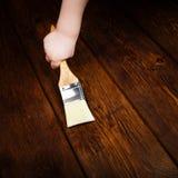 Dziecko ręka stosuje ochronnego lakier na drewnianym stole fotografia stock