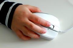 Dziecko ręka z komputerową myszą na bielu stole Fotografia Royalty Free