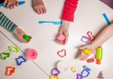 Dziecko ręki bawić się z plasteliną Zdjęcia Stock