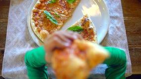 Dziecko ręki bierze plasterek pizza od białego talerza w restauracji, kawiarnia Zakończenie Chłopiec lub dziewczyny wp8lywy pizza zbiory