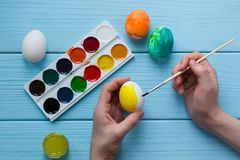 Dziecko ręki malują Wielkanocnego jajko żółtą kolor farbą i farby, paintbrush, malowali Wielkanocnych jajka Zdjęcia Stock