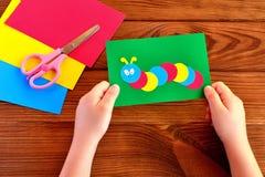 Dziecko ręki trzyma papierowej aplikacyjnej gąsienicy Papier ciąć na arkusze, nożyce na brown drewnianym tle Obrazy Royalty Free