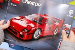 Dziecko ręki z Lego instrukcją set 10248 Ferrari F40 Fotografia Stock