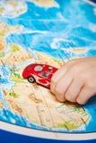 Dziecko ręka z zabawkarskim samochodem na mapie Afryka Zdjęcia Stock