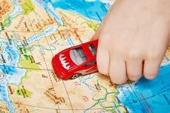 Dziecko ręka z zabawkarskim samochodem na mapie Afryka Fotografia Royalty Free