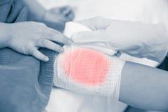 Dziecko raniący Doktorski bandażuje dziecka ` s kolano Ludzka opieka zdrowotna a Zdjęcie Stock