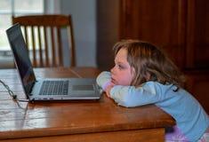 Dziecko relaksuje przy sto?em z laptopem, ogl?da dzieciak piosenki wideo zdjęcie stock