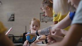 Dziecko remis z ołówkami Ucznie z nauczycielem siedzą przy stołem indoors i rysują na białym papierze z barwionymi ołówkami zdjęcie wideo