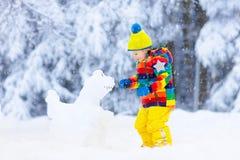 Dziecko robi bałwanu Dzieciak sztuka w śniegu w zimie zdjęcia stock