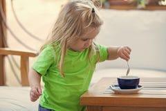 Dziecko robi kawie dla jego matki Dziecko chłopiec z blond długie włosy miesza cukierem z teaspoon Zdjęcie Stock