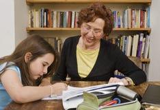 dziecko robi praca domowa halping seniora Zdjęcia Royalty Free