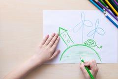 Dziecko rysuje z barwionymi ołówkami zielonego dom, elektrycznego samochód i wietrzną elektrownię, pojęcie ekologia fotografia royalty free