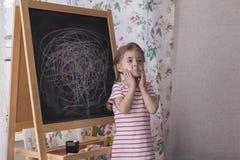 Dziecko rysuje z kawałkami kolor kreda na kredowej desce Dziewczyna wyraża twórczość i patrzeje kamerę zdjęcia royalty free