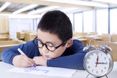 Dziecko rysunek w klasie z zegarem na biurku Fotografia Stock