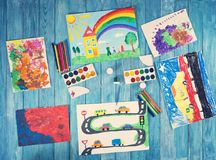 Dziecko rysunki z remisów akcesoriami na błękitnym drewnianym tle Obrazy Stock