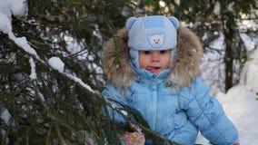 Dziecko rzuca z śniegu od gałąź w słonecznym dniu zbiory
