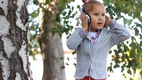 Dziecko słucha muzyka i śpiew w hełmofonach piosenka w parku z brzozami zbiory