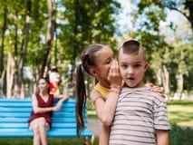 Dziecko sekrety za matką z powrotem przy parkiem obrazy stock