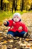 Dziecko siedzi na żółtych liściach obrazy stock