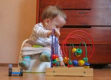 Dziecko siedzi na garnku i sztuk zabawkach Wesoło chłopiec uczy się Zdjęcie Stock