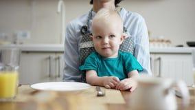 Dziecko siedzi na matka podołku andlooking wokoło i niej bawić się z on z przekroczenie kosztów kamerą zbiory