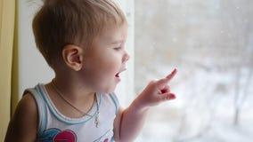 Dziecko siedzi na parapecie out i przyglądający śnieżny zakończenie okno zbiory wideo