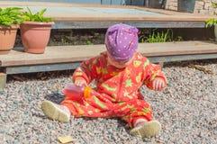 Dziecko siedzi na skałach i nalewa z dziecko butelki napojem, Zdjęcia Stock