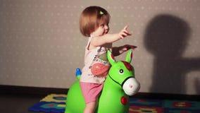 Dziecko siedzi na zabawkarskim koniu zdjęcie wideo
