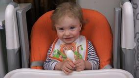 Dziecko siedzi w dziecka siedzeniu przy stołem zbiory wideo